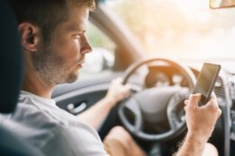 Man busy texting while driving.