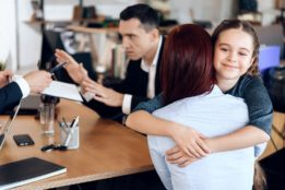 Little girl hugging her mom in lawyers office.