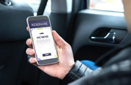 Passenger using ridesharing app in his mobile phone.