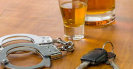 Drunk driving concept with car keys, handcuff and liquor.